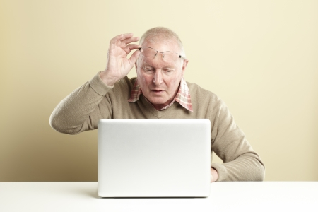 Senior man using laptop whilst looking confused photo