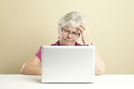 Senior woman using laptop whilst looking confused photo