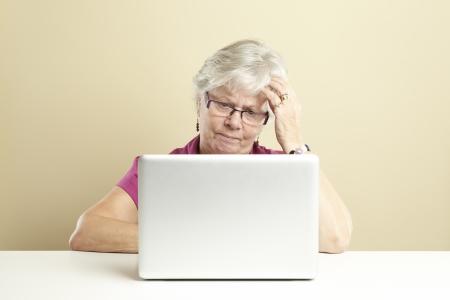 one senior adult woman: Superior de la mujer usando la computadora port�til, mientras que mirando confundido Foto de archivo