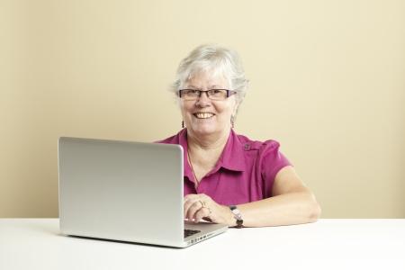 Senior woman using laptop whilst smiling Stock Photo - 14615944
