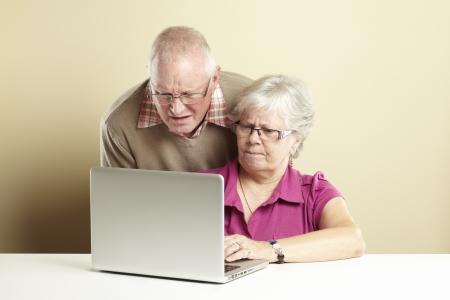 persona confundida: Hombre mayor y mujer que usa ordenador portátil, mientras que mirando confundido