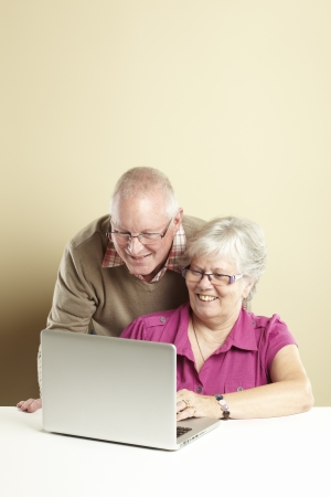 old pc: Senior man and woman using laptop whilst looking happy
