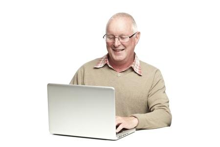 Senior man met behulp van laptop, terwijl glimlachen, op een witte achtergrond