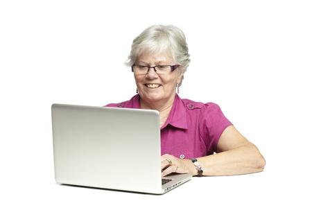 gladly: Mujer mayor que usa la computadora port�til mientras sonriente, sobre fondo blanco