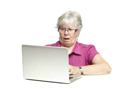 Senior woman using laptop whilst looking shocked, on white background photo