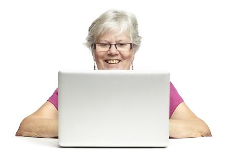 operates: Anziano, donna, utilizzando il computer portatile, mentre sorridente, su sfondo bianco Archivio Fotografico
