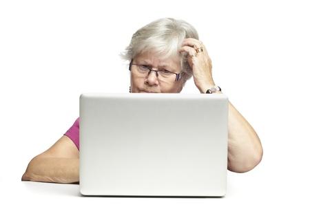 persona confundida: Mujer mayor que usa la computadora portátil mientras que parece confundido, sobre fondo blanco