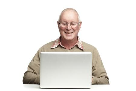 Senior man met behulp van laptop, terwijl lachend, op een witte achtergrond