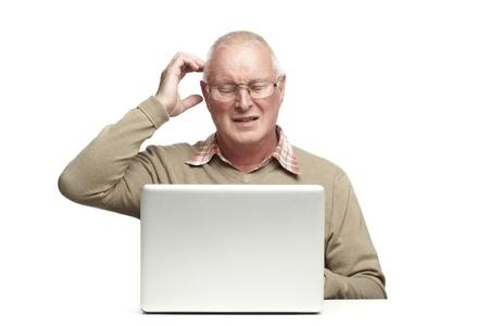 Senior man met behulp van laptop, terwijl zoek verward, op witte achtergrond