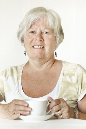 gladly: Sonriente se�ora mayor sentada a la mesa con una taza de t�