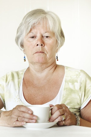teas: Thoughtful Senior lady sitting at table holding a cup of tea