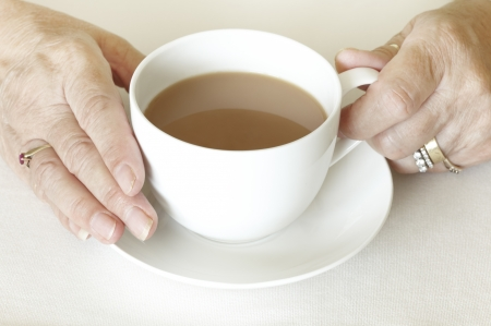 Senior womans hands holding a cup of tea on white table cloth Stock Photo - 14652257