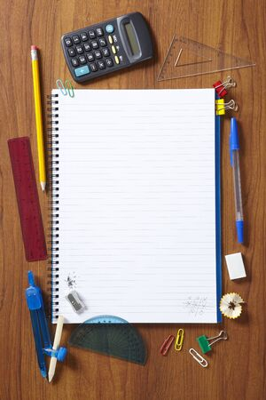 note pad: Back to School pupils note pad and stationary on wooden school desk from above