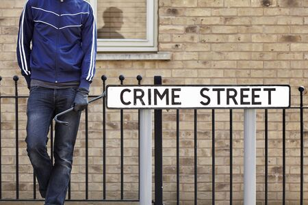 Burglar standing on street with crowbar and leather gloves next to crime street road sign photo