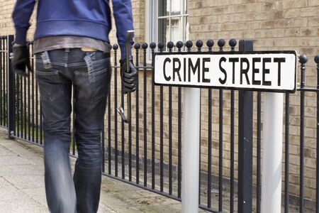 illegally: Burglar standing on street with crowbar and leather gloves next to crime street road sign Stock Photo