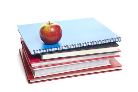 produits alimentaires: Livres scolaires entassés avec une pomme sur le dessus sur fond blanc