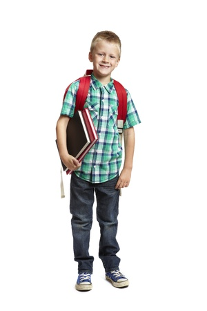 8 year old school boy with backpack holding books on white background photo