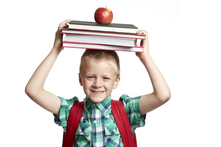 8 year old school boy with backpack books and apple on his head on white background