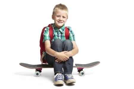 8 year old school boy with backpack sitting on a skateboard on white background
