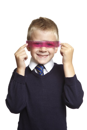 8 year old: 8 year old school boy with pink ruler over his eyes on white background