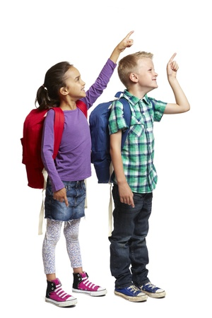 joyfully: 8 year old school boy and girl with backpacks pointing and smiling on white background