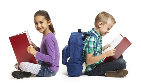 8 year old school boy and girl sitting reading with backpacks on white background Stock Photo