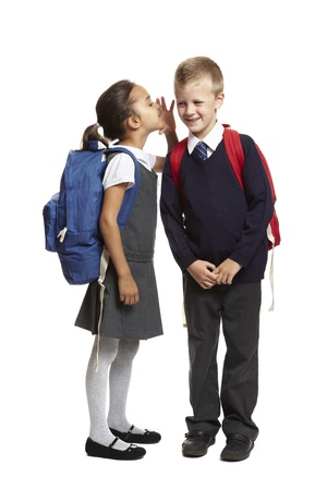 8 year old school girl with backpack whispering in boys ear smiling on white background
