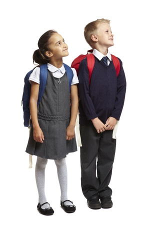 8 year old school boy and girl with backpacks looking up on white background photo