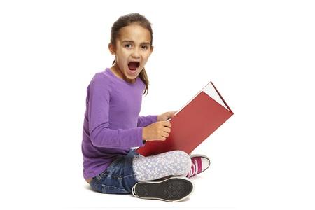 asombro: 8 años niña de la escuela sentada libro de lectura mirando sorprendido sobre fondo blanco