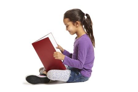 8-jarige schoolmeisje zit te lezen boek glimlachend op witte achtergrond
