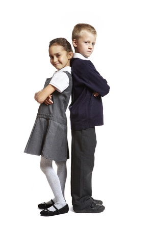 unifrom: 8 year old school boy and girl stood back to back on white background