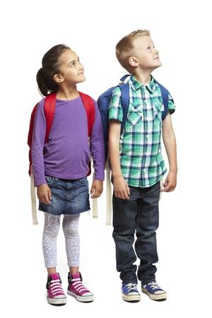 8 jaar oude school jongen en meisje te kijken op witte achtergrond Stockfoto