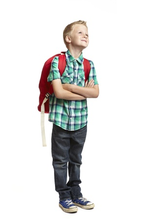 8 year old school boy with backpack looking up on white background