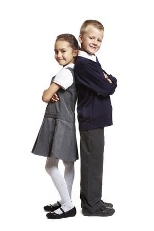 8 jaar oude school jongen en meisje stond rug aan rug op een witte achtergrond