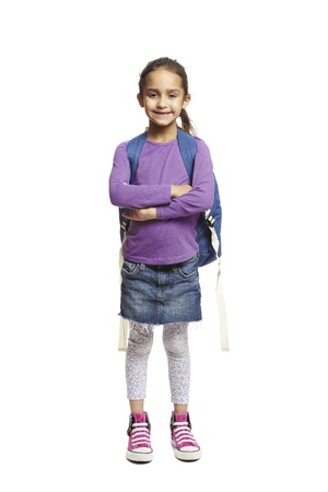 8 year old school girl arms folded with backpack smiling on white background Stock Photo