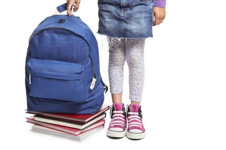 8 year old school girl with books and backpack on white background