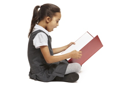 sat: 8 year old school girl sitting reading book looking shocked on white background Stock Photo