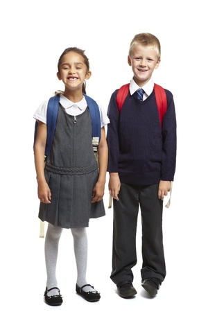 8 year old school boy and girl with backpacks smiling on white background photo