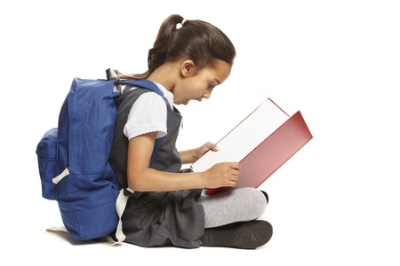 bambini che leggono: 8 school girl anni seduto libro di lettura con zaino guardando scioccata su sfondo bianco