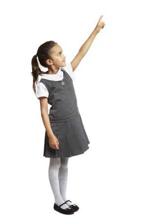 8 year old school girl pointing up smiling on white background