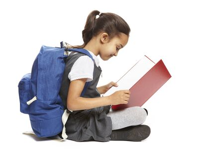school uniform: 8 year old school girl sitting reading book with backpack smiling on white background