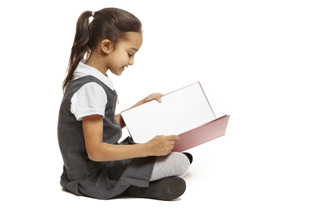 8 year old: 8 year old school girl sitting reading book smiling on white background
