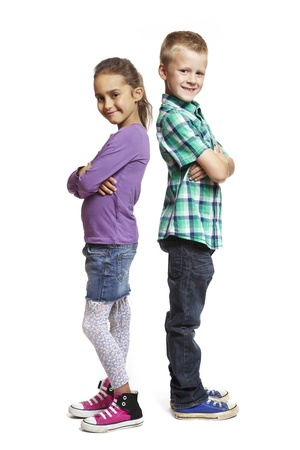 two boys: 8 year old boy and girl stood back to back on white background Stock Photo