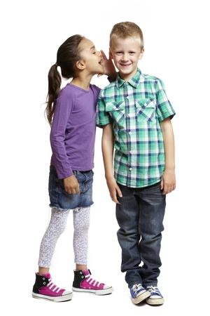 8-jarig meisje fluistert in jongens oor glimlachen op een witte achtergrond