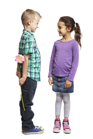 8 year old boy giving pink flower to girl on white background Stock Photo