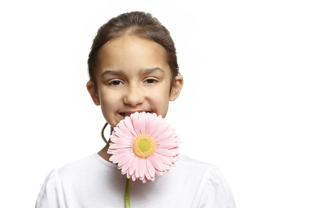 8 year old girl: 8 year old girl smiling with pink flower on white background Stock Photo