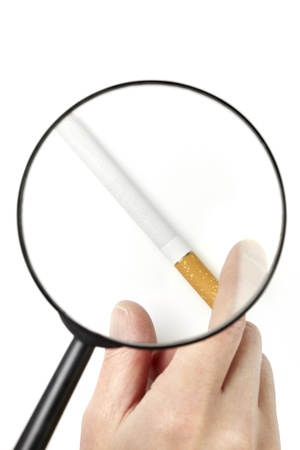 warns: Hand taking cigarette viewed through magnifying glass isolated on white background Stock Photo