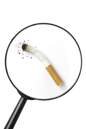 risking: Stubbed out cigarette viewed through magnifying glass isolated on white background Stock Photo