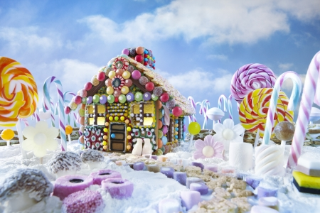 Peperkoek huis in kerst landschap, omgeven door zuurstokken en snoep