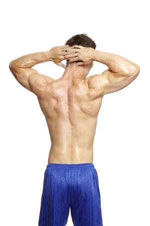 Gespierde jonge man buigen armspieren in de sport outfit op witte achtergrond